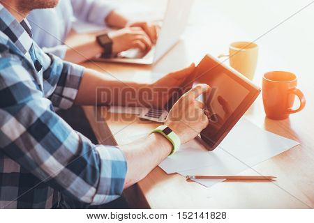 One touch. Pleasant man sitting  at the table with his colleague and holding tablet while working
