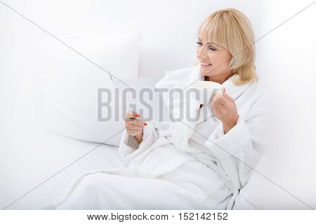 Joyful mature woman is relaxing on vacation. She is reading magazine and drinking tea. Woman is sitting on sofa and smiling