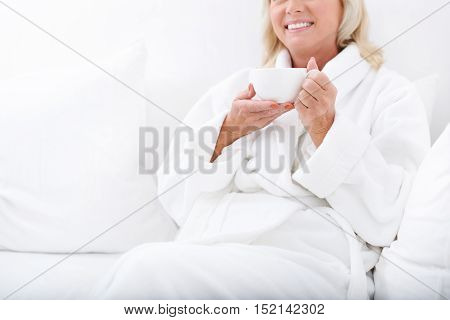 Dreamful mature woman is relaxing on spa resort. She is drinking coffee and smiling. Woman is sitting on sofa in bathrobe
