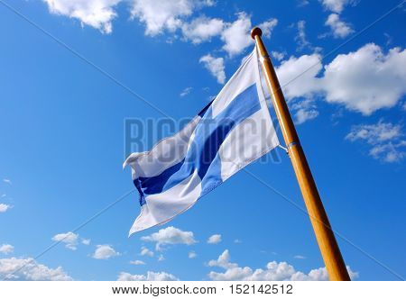 Flag of Finland on a wooden flagpole blue sky.