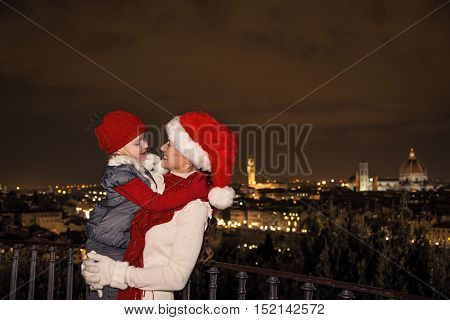 Smiling Mother And Child In Christmas Hats In Florence Embracing