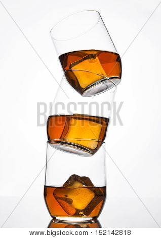 Glasses of whiskey with ice cubes with reflection on white background
