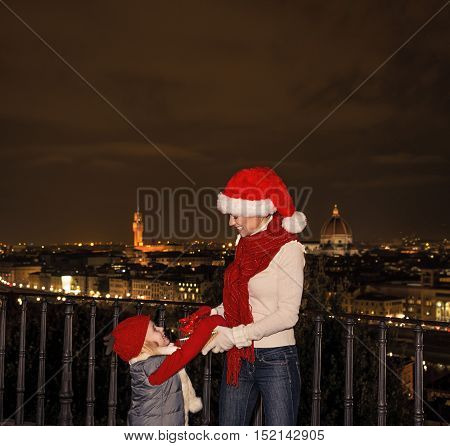Mother And Daughter In Christmas Hats In Florence, Italy Playing