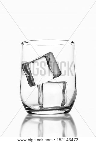 Empty whiskey glass with ice cubes with reflection on white background