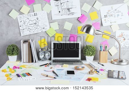 Creative designer desktop with blank laptop other gadgets financial reports construction sketches numerous colorful supplies stickers and other items. Mock up. Modern workplace concept