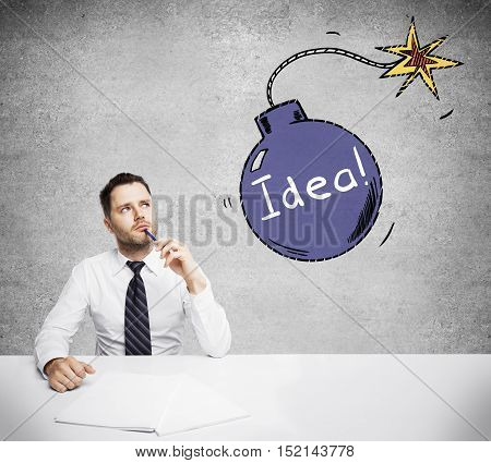 Thoughtful businessman at workplace with creative bomb sketch on concrete wall background. Idea concept