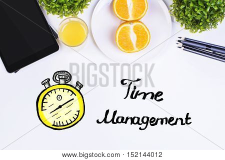 Top view of white table with electronic devices decorative plant orange halves supplies and creative clock sketch. Time management concept