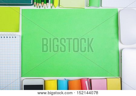 Top view of office desktop with bright coloured paper sheet other supplies and smartphone. Mock up