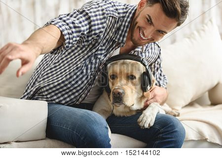 handsome smiling man showing something to his dog who wearing headphones indoors