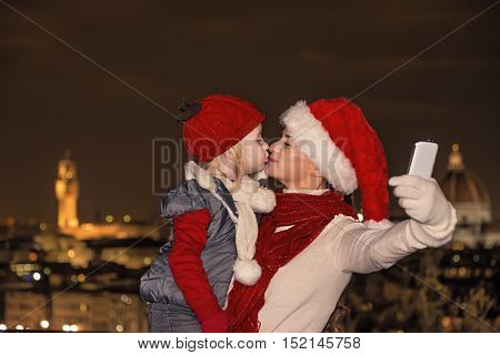 Mother And Child In Christmas Hats Taking Selfie And Kissing