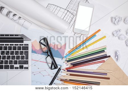 Top view of blank white smartphone laptop financial reports glasses and colorful supplies on office desktop. Mock up