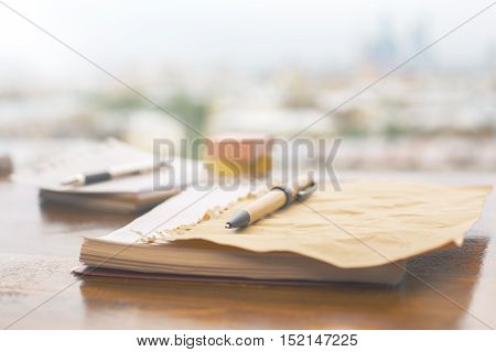 Closeup of pen and notepad on blurry background