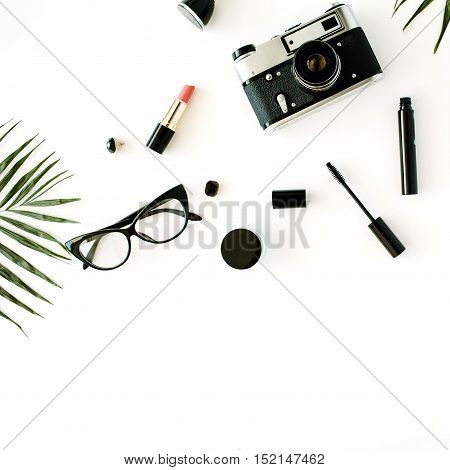 flat lay feminine arrangement with retro camera accessories glasses cosmetics and palm branches on white flat lay top view