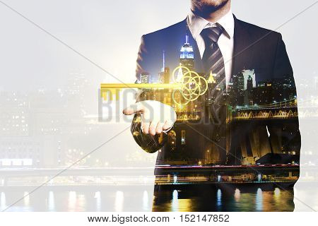 Businessman holding ornate golden key on night city background with copy space. Double exposure