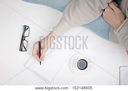 Top view of girl's hand writing in notepad placed on white surface with coffee cup and other items. Mock up
