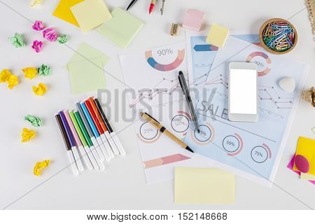 Top view of messy office desktop with colorful supplies business report and blank white smartphone. Mock up