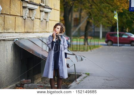 Lovely modern girl in a colorful scarf and cloak standing near the wall of house in the old St Petersburg courtyard