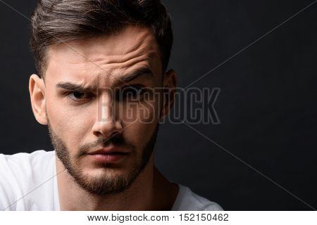 portrait of surprised man's face with copy space against the dark background