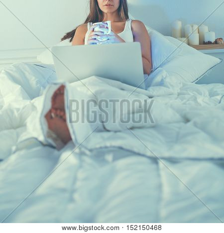 A pretty young woman with laptop in bed and enjoying a cup of tea.
