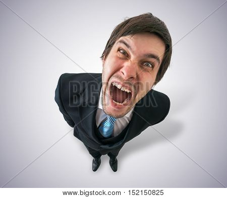 Young Crazy Businessman Or Boss Is Screaming. View From Top.