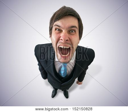 Young funny mad businessman or boss is shouting. View from top.