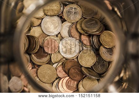 a jar full of coins, with the classic piggy bank in the foreground two euro, the European currency to fight crisis