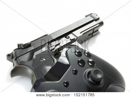 Close up studio shot of a game controller and a real handgun near it