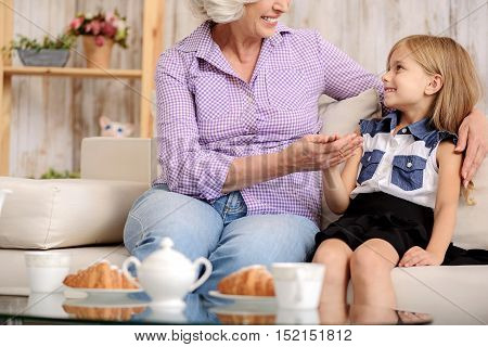 Joyful grandmother is looking after her granddaughter. They are sitting on couch near food and drink. Family is embracing and smiling