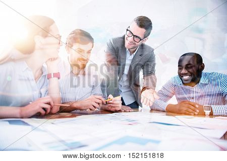 Here is solution. Handsome bearded man showing results of creative work in light office to his colleagues.