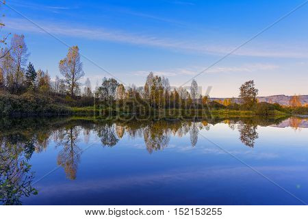 Beautiful fall landscape with blue sky reflected in the water. Wooded waterside of tranquil lake. Fall idyllic landscape.