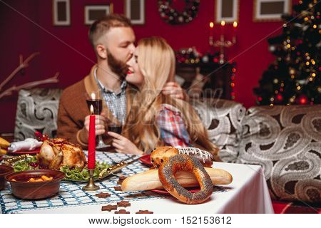 Beautiful Couple Kissing And Holding Glass Of Wine In A Decorated Festive Interior With A Christmas