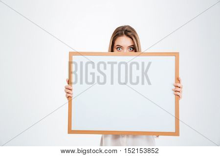 Young woman with eyes wide open peeping from blank board isolated on a white background
