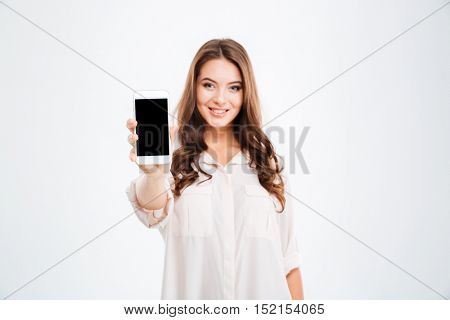 Portrait of a smiling woman showing blank smartphone screen isolated on a white background