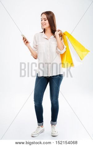 Full length portrait of a happy young woman holding shopping bags and mobile phone isolated on a white background