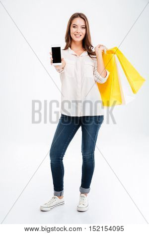 Full length portrait of a smiling young woman showing blank screen smrtphone and holding bags isolated on a white background