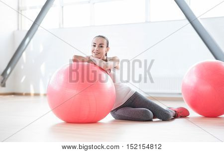 Having a rest. Positive well built young woman lying on the floor and leaning on a fitness ball while being in a gym hall