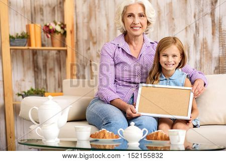 This is our family portrait. Cheerful little girl and her grandmother are showing frame to camera. They are sitting and smiling. Mature woman is sitting on couch and embracing granddaughter