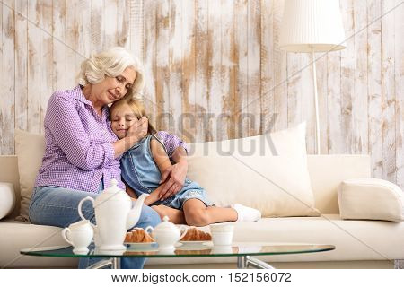 Mature woman is embracing her granddaughter with love. They are is sitting on couch with relaxation