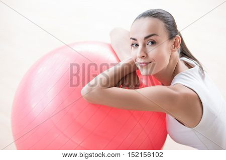 During fitness training. Pleasant beautiful joyful woman leaning on a pink fitness ball and smiling while having a workout