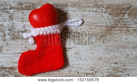 Give your heart to someone special at Christmas time! Heart as a tender gift inside of colorful knitted Christmas stocking.