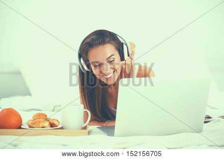 Young beautiful woman in bed listening to music.