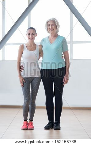 We love sports. Joyful nice pleasant women standing together and smiling while having a workout