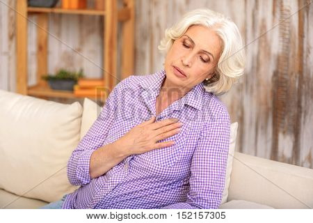 Old woman is suffering from heartache. She is sitting on sofa and touching breast with frustration