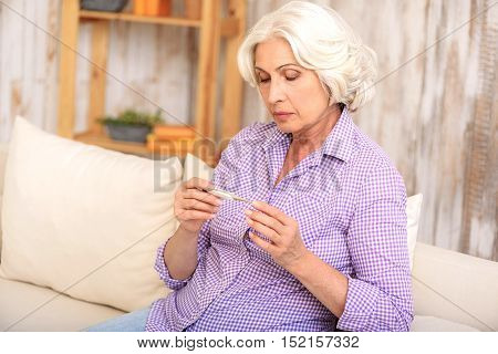 Sick old woman is measuring her temperature. She is sitting on couch and looking at thermometer with sadness