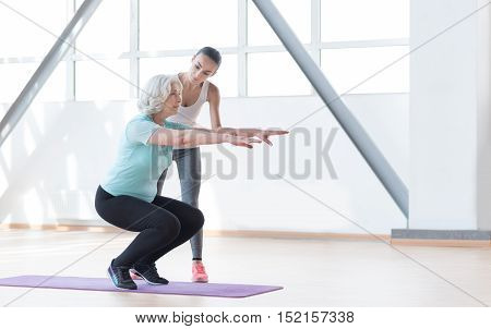 Think about your health. Serious good looking persistent woman standing on a mat and squatting while working out with a coach