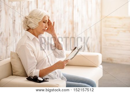 Senior lady is suffering from headache while reading newspaper. She is sitting and touching head with frustration. Pressure gauge on sofa