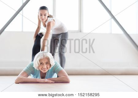 During a fitness workout. Joyful confident old woman lying on the mat and holding her leg up while looking at you