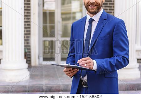 bearded man in suit writing in a tablet outdoors, close up