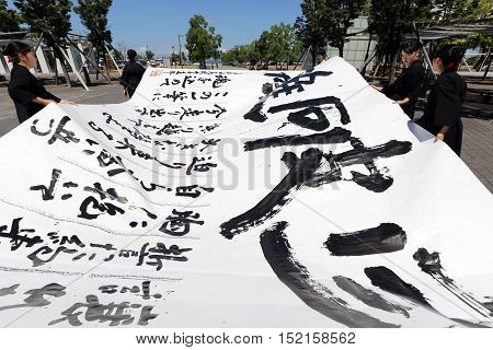 KAGAWA, JAPAN- AUGUST 21, 2016 : Japanese schoolgirls competes for the written technology in a Kagawa Calligraphy Festival 2016.