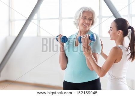 Physical strength. Pleasant confident joyful woman holding rubber dumbbells and lifting them while building up her muscles